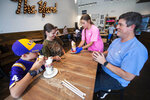 From left, Xander Hall, 9, of Prairieville, La., and his mother Nikki Hall, get served by Angelina Trancina, 17, with Xander's father John Hall at The Yard Milkshake Bar, Tuesday, July 13, 2021 in Baton Rouge, La. To say The Yard Milkshake Bar serves over-the-top confections is a bit of an understatement. This is the description for its Tiger Deaux milkshake unique to Baton Rouge: a concoction of cookie dough ice cream with purple and gold marshmallow cream served in a vanilla iced jar rolled in purple and gold sprinkles and topped with purple and gold whipped cream, a scoop of chocolate chip cookie dough, more sprinkles and a purple tiger paw.(Travis Spradling/The Advocate via AP)