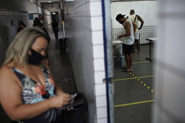 Locals vote at a polling station during run-off municipal elections in Rio de Janeiro, Brazil, Sunday, Nov. 29, 2020. (AP Photo/Silvia Izquierdo)