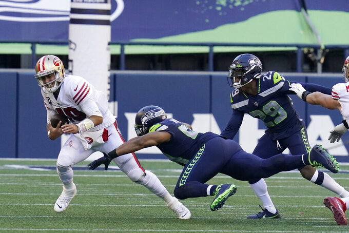 San Francisco 49ers quarterback Jimmy Garoppolo, left, is sacked by Seattle Seahawks middle linebacker Bobby Wagner, center, as D.J. Reed (29) looks on during the first half of an NFL football game, Sunday, Nov. 1, 2020, in Seattle. (AP Photo/Elaine Thompson)