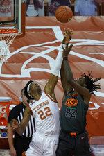 Texas' Kai Jones, left, blocks a shot by Oklahoma State's Kalib Boone, right, during the first half of an NCAA college basketball game in Austin, Texas, Sunday, Dec. 20, 2020. (AP Photo/Chuck Burton)
