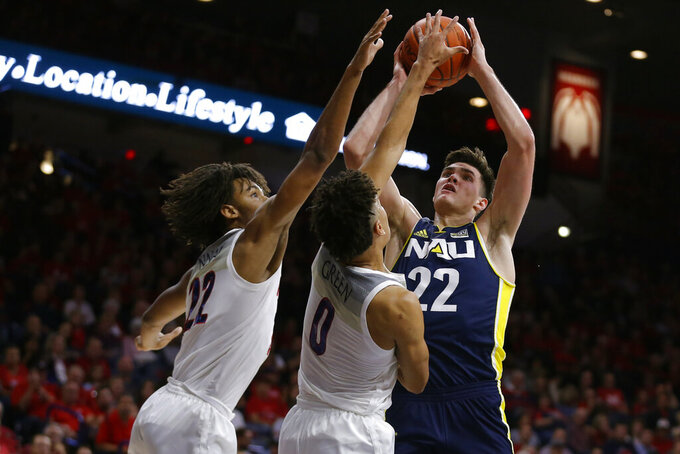 Northern Arizona forward Brooks DeBisschop (22) shoots over Arizona's Zeke Nnaji (22) and Josh Green during the first half during an NCAA college basketball game Wednesday, Nov. 6, 2019, in Tucson, Ariz. (AP Photo/Rick Scuteri)
