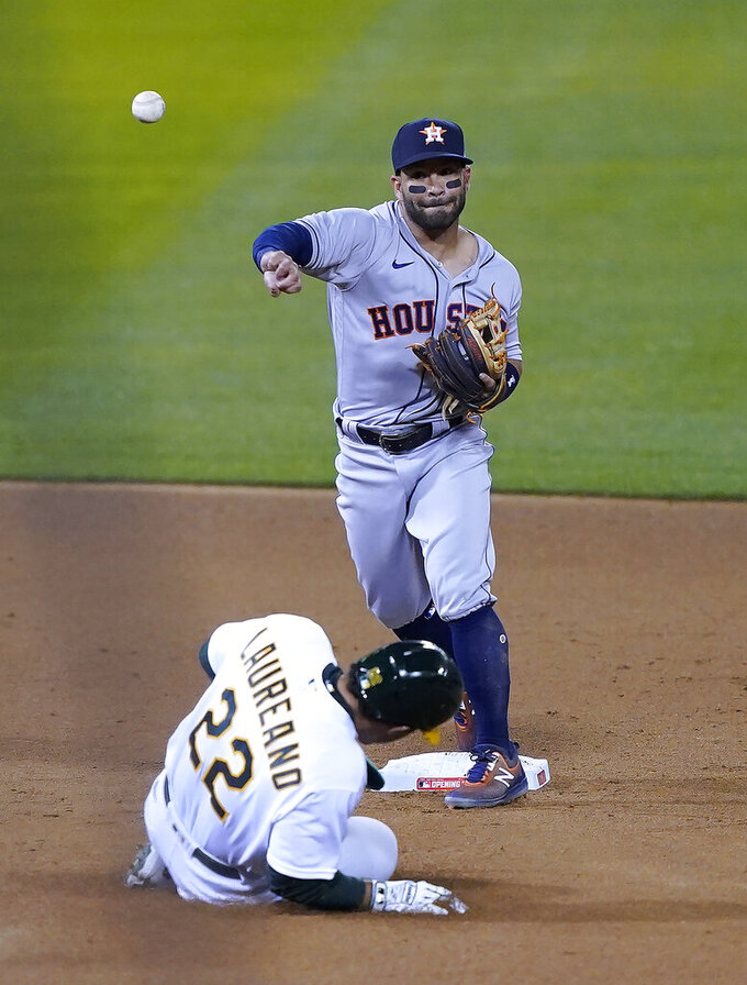 Houston Astros second baseman Jose Altuve (27) throws to first for the double play on a ball hit by Oakland Athletics' Matt Chapman (not shw=own) after forcing Ramon Laureano (22) out at second during the fourth inning of a baseball game in Oakland, Calif., Thursday, April 1, 2021. (AP Photo/Tony Avelar)