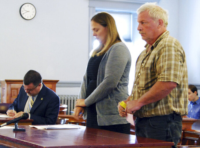 FILE - In this Aug. 17, 2017, file photo, Mark Johnson, right, stands next to public defender Rosie Chase, center, during his arraignment in North Hero, Vt., on charges he sprayed liquid manure on a marked U.S. Customs and Border Protection car on Aug. 3 in Alburgh, Vt., after confronting an agent about immigration enforcement. The Vermont man has pleaded guilty to charges that he sprayed liquid cow manure on a U.S. Customs and Border Protection car after confronting an agent about why he wasn't doing more to arrest people in the country illegally. (Tonya Poutry/The Islander via AP, Pool, File)