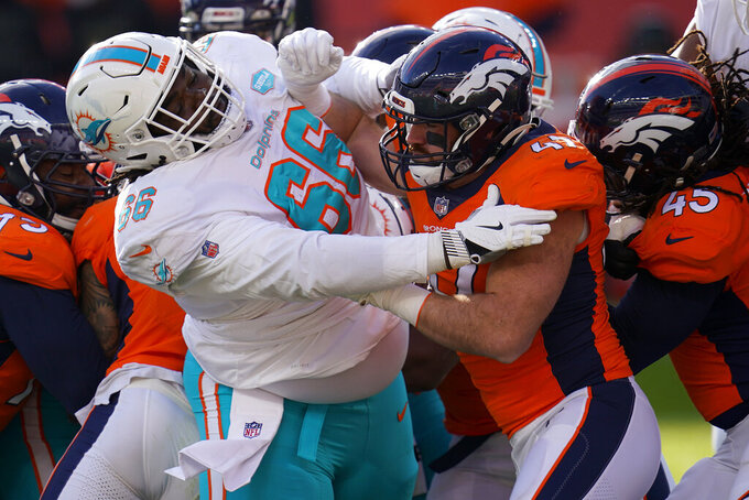 Denver Broncos inside linebacker Josey Jewell, right, battles Miami Dolphins offensive guard Solomon Kindley (66) during the first half of an NFL football game, Sunday, Nov. 22, 2020, in Denver. (AP Photo/David Zalubowski)