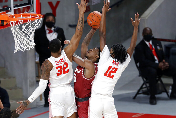 Temple guard Jeremiah Williams, middle, goes up for a basket between Houston forward Reggie Chaney (32) and guard Tramon Mark (12) during the first half of an NCAA college basketball game Tuesday, Dec. 22, 2020, in Houston. (AP Photo/Michael Wyke)