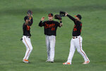 Baltimore Orioles outfielders Cedric Mullins, left, Austin Hays, center, and Anthony Santander celebrate after defeating the Tampa Bay Rays 6-3 during a baseball game early Saturday, Aug. 1, 2020, in Baltimore. (AP Photo/Julio Cortez)