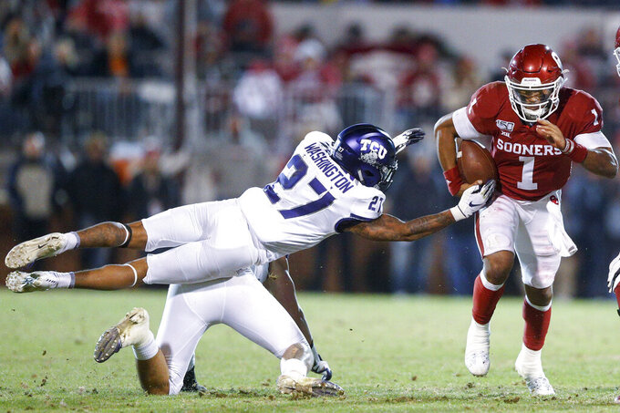 Oklahoma quarterback Jalen Hurts (1) avoids an attempted tackle by TCU safety Ar'Darius Washington (27) and linebacker Garret Wallow during an NCAA college football game Saturday, Nov. 23, 2019, in Norman, Okla. (Ian Maule/Tulsa World via AP)