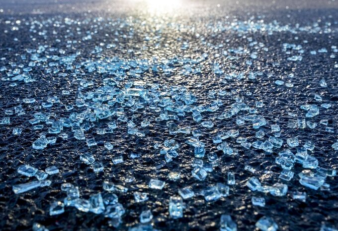 Broken glass from the window of a car in which a man was shot lies scattered on the street in Hanau, Germany on Friday, Feb. 21, 2020, two days after a 43-year-old German shot and killed several people at several locations in the Frankfurt suburb. Tobias Rathjen had left rambling texts and videos in which he espoused racist views, called for genocide and claimed to have been under surveillance since birth. (AP Photo/Michael Probst)