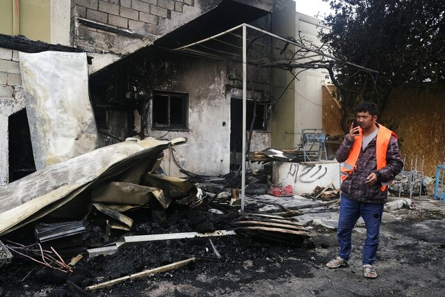 A man stands next to a burned installation which built for migrants, on the northeastern Aegean island of Lesbos, Greece, Sunday, March 8, 2020. A fire broke out at a refugee center on Lesbos island, Greece's firefighting service said Sunday, causing considerable damage to a warehouse but no injuries. (AP Photo/Alexandros Michailidis)