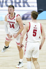 Wisconsin's Brad Davison (34) celebrates with Tyler Wahl (5) after Davison hit s shot during the second half of an NCAA college basketball game against Penn State at the Big Ten Conference tournament, Thursday, March 11, 2021, in Indianapolis. (AP Photo/Darron Cummings)