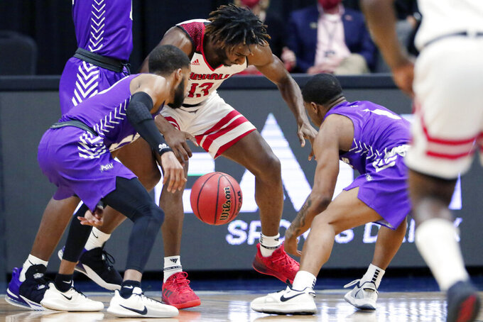 Nicholls State guard Andre Jones (13) goes for a loose ball between Abilene Christian guards Reggie Miller, left, and Damien Daniels during the first half of an NCAA college basketball game for the Southland Conference men's tournament championship Saturday, March 13, 2021, in Katy, Texas. (AP Photo/Michael Wyke)