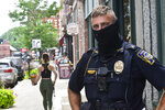 Brattleboro, Vt., Police Officer Jason Hamilton patrols around Brattleboro while wearing a mask on Friday, July 24, 2020. Vermont Gov. Phil Scott said in a press conference that starting Aug. 1, masks will be mandatory in public.  (Kristopher Radder/The Brattleboro Reformer via AP)
