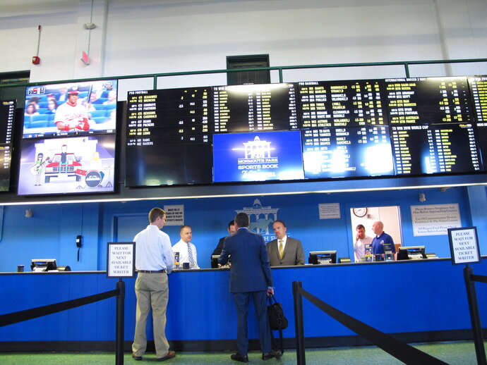 This June 14, 2018 photo shows staff at Monmouth Park racetrack in Oceanport N.J. preparing to begin taking sports bets moments before it became legal in New Jersey. State gambling regulators on Thursday July 12, 2018 were to reveal how the state's sports betting market did in its first two weeks. (AP Photo/Wayne Parry)