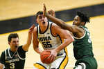 Iowa center Luka Garza (5) drives to the basket between Michigan State guard Foster Loyer, left, and forward Julius Marble II, right, during the second half of an NCAA college basketball game, Tuesday, Feb. 2, 2021, in Iowa City, Iowa. Iowa won 84-78. (AP Photo/Charlie Neibergall)