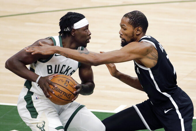 Milwaukee Bucks' Jrue Holiday, left, drives to the basket against Brooklyn Nets' Kevin Durant during the first half of an NBA basketball game Tuesday, May 4, 2021, in Milwaukee. (AP Photo/Aaron Gash)