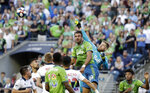 Vancouver Whitecaps goalie Zac MacMath, center right, taps away the ball behind Seattle Sounders' Justin Dhillon during the first half of an MLS soccer match Saturday, June 29, 2019, in Seattle. (AP Photo/Elaine Thompson)