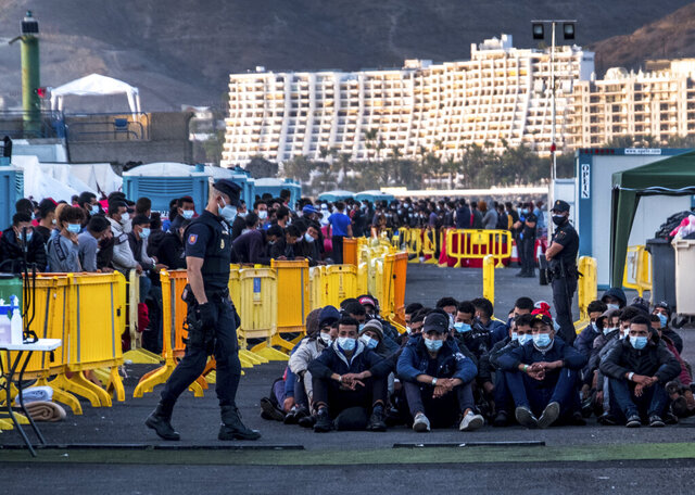Migrants stand at the Arguineguin port in Gran Canaria island, Spain, after being rescued in the Atlantic Ocean by emergency workers on Thursday, Oct. 19, 2020. Under increasing pressure from the steady build-up of Africans' arrivals to its southern Canary Islands, the Spanish government has launched an all-front offensive, including active diplomacy, to avoid becoming the next black spot on Europe's failing record handling migration flows. (AP Photo/Javier Bauluz)