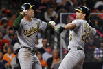 Oakland Athletics' Matt Olson, right, celebrates his three-run home run with Mark Canha during the eighth inning of a baseball game against the Houston Astros, Friday, April 9, 2021, in Houston. (AP Photo/Eric Christian Smith)