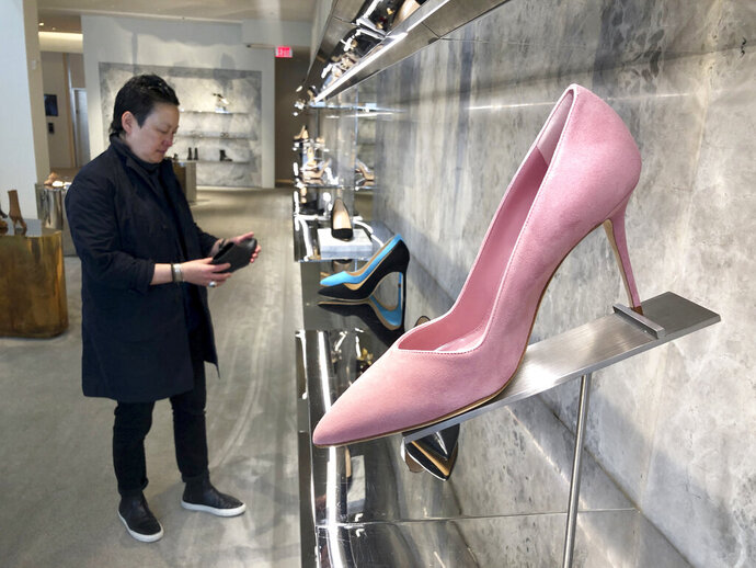 FILE - In this June 12, 2019, file photo, personal shopper and stylist Kat Yeh looks at shoes for a client in San Francisco. One of the fastest-growing job categories of the past decade has been in what economists call
