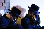 Orthodox Jewish men mourn during the funeral service of Mindel Ferencz who was killed in a kosher market that was the site of a gun battle in Jersey City, N.J., Wednesday, Dec. 11, 2019. Ferencz, 31, and her husband owned the grocery store. The Ferencz family had moved to Jersey City from Brooklyn. (AP Photo/Eduardo Munoz Alvarez)