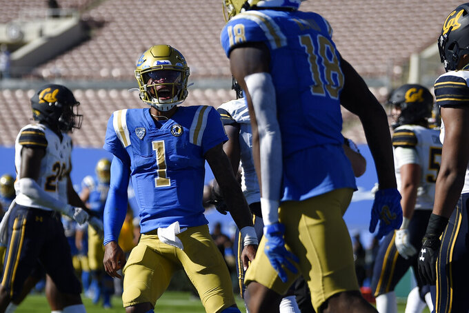 UCLA quarterback Dorian Thompson-Robinson, front left, celebrates a touchdown by Charles Njoku during the first half of an NCAA college football game against California in Los Angeles, Sunday, Nov. 15, 2020. (AP Photo/Kelvin Kuo)