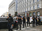 Police officers block an area near a city bank in Kyiv, Ukraine, Monday, Aug. 3, 2020, after a man has threatened to blow up an explosive device inside the bank. The man, identified as Sukhrob Karimov, a 32-year-old citizen of the Central Asian nation of Uzbekistan, entered a bank office in Kyiv and said he had explosives in his backpack. He let bank clerks go and demanded that the authorities invite journalists so that he could make a statement. (AP Photo/Efrem Lukatsky)