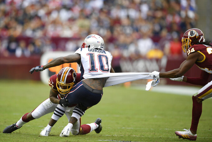 Washington Redskins cornerback Quinton Dunbar (23) and Washington Redskins cornerback Josh Norman (24) tackle New England Patriots wide receiver Josh Gordon (10) during the second half of an NFL football game, Sunday, Oct. 6, 2019, in Washington. (AP Photo/Nick Wass)
