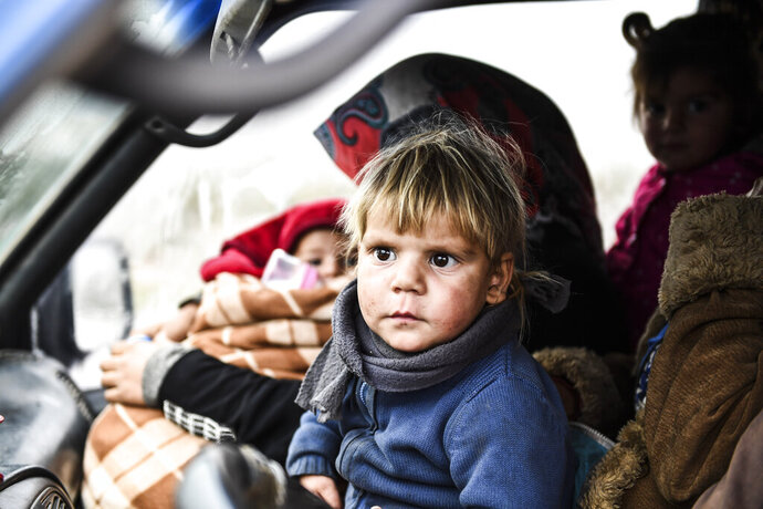 Syrian civilians flee from Idlib in rain toward the north to find safety inside Syria near the border with Turkey, Thursday, Feb. 13, 2020. Syrian troops are waging an offensive in the last rebel stronghold according to news reports by a Turkish news agency.( AP Photo)