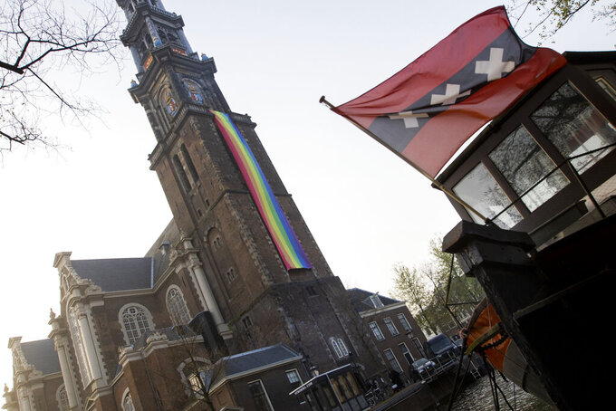 A large rainbow flag flies from the bell tower of Wester Church to mark the 20th anniversary of the first legalized same-sex marriage in Amsterdam, Netherlands, Thursday, April 1, 2021. Twenty years ago, the mayor of Amsterdam married four couples in City Hall as the Netherlands became the first country in the world with legalized same-sex marriage. It's now legal in 28 countries. The three crosses of the coat of arms of the city of Amsterdam are seen on a houseboat at right. (AP Photo/Peter Dejong)