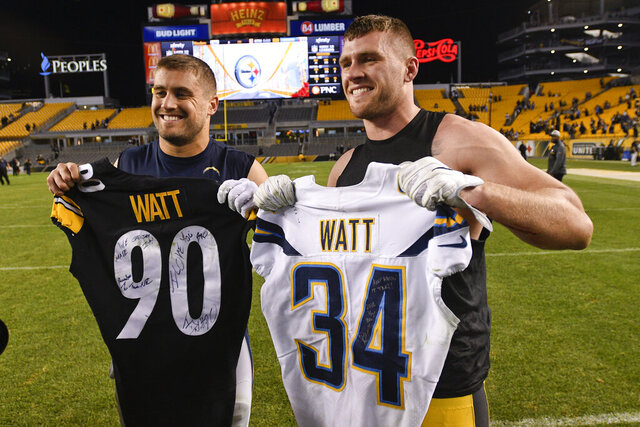 FILE - In this Dec. 2, 2018, file photo, Pittsburgh Steelers outside linebacker T.J. Watt, right, and Los Angeles Chargers fullback Derek Watt pose after exchanging jerseys after an NFL football game in Pittsburgh. Derek Watt couldn't pass up the opportunity to play with his younger brother T.J. It's the main reason the fullback agreed to a three-year contract with the Pittsburgh Steelers.(AP Photo/Don Wright, File)