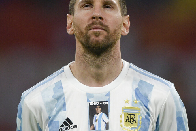 Argentina's Lionel Messi wears a jersey with the number and image of late soccer star Diego Maradona prior to a FIFA World Cup Qatar 2022 qualifying soccer match against Chile in Santiago del Estero, Argentina, Thursday, June 3, 2021. (Juan Mabromata, Pool via AP)