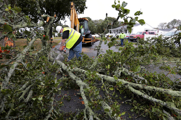 Jay Desorcy, left, and Dwayne Pinkham, of New Bedford DPI Green Space, cut a large section of a tree that fell due to the high winds across Kenney Street in the north end of New Bedford, Mass., Wednesday, Sept. 30, 2020. (Peter Pereira/The Standard-Times via AP)