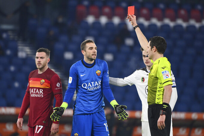 Referee Davide Ghersini, right, shows the red card against Roma's goalkeeper Pau Lopez, center, during the Italian Cup, round of 16 soccer match between Roma and Spezia at the Olympic stadium in Rome, Tuesday, Jan. 19, 2021. (Alfredo Falcone/LaPresse via AP)
