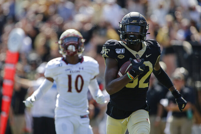Wake Forest wide receiver Jaquarii Roberson, right, runs for the end zone to score ahead of Elon defensive back Tre'Von Jones (10) in the first half of an NCAA college football game in Winston-Salem, N.C., Saturday, Sept. 21, 2019. (AP Photo/Nell Redmond)