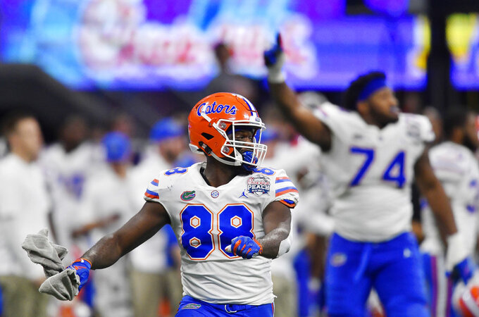 Florida tight end Kemore Gamble (88) and Florida offensive lineman Fred Johnson (74) celebrate after the Peach Bowl NCAA college football game against Michigan, Saturday, Dec. 29, 2018, in Atlanta. Florida won 41-15. (AP Photo/Mike Stewart)