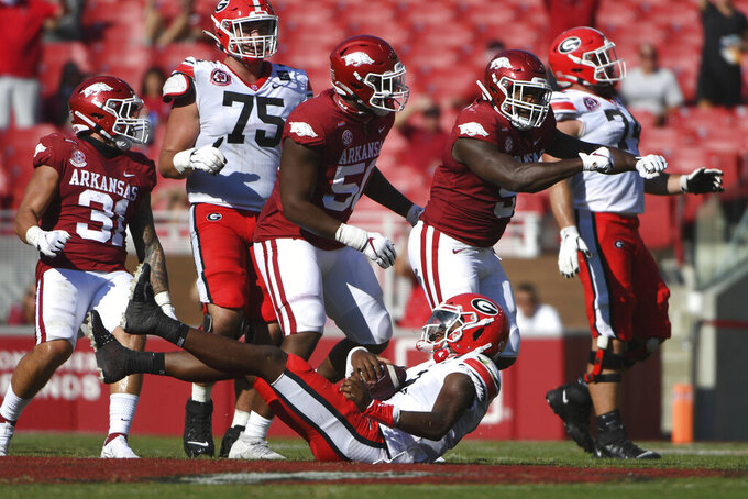 Arkansas defenders Grant Morgan (31), Eric Gregory, (50) and Dorian Gerald (5) celebrate after bringing down Georgia quarterback D'Wan Mathis (2) for a loss during the first half of an NCAA college football game in Fayetteville, Ark., Saturday, Sept. 26, 2020. (AP Photo/Michael Woods)