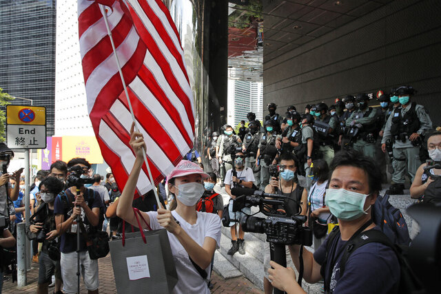 FILE - In this July 4, 2020, file photo, a woman carries an American flag during a protest outside the U.S. Consulate in Hong Kong. The U.S. has issued a new advisory Tuesday, Sept. 15, 2020, warning against travel to mainland China and Hong Kong, citing the risk of