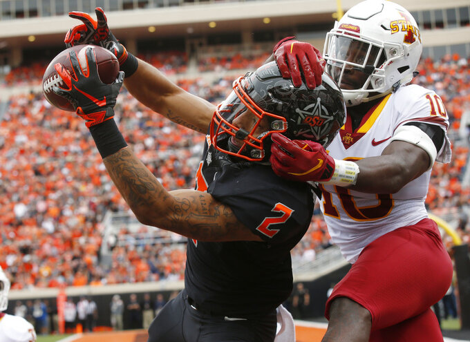 FILE - In this Saturday, Oct. 6, 2018, file photo, Oklahoma State wide receiver Tylan Wallace (2) reaches for but can't hold onto the pass as Iowa State defensive back Brian Peavy (10) defends in the first half of an NCAA college football game in Stillwater, Okla. Wallace is second in the Big 12 with 102.6 yards receiving per game, with 40 catches for 718 yards and four TDs.  (AP Photo/Sue Ogrocki, File)