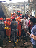 This photograph provided by India's National Disaster Response Force (NDRF) shows NDRF personnel rescuing a survivor after a residential building collapsed in Bhiwandi in Thane district, a suburb of Mumbai, India, Monday, Sept.21, 2020. (National Disaster Response Force via AP)