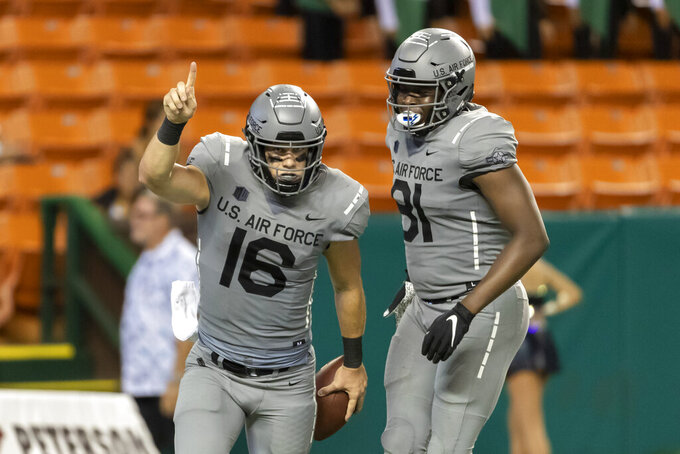 Air Force quarterback Mike Schmidt (16) celebrates scoring a touchdown with his teammate tight end Lesley Dalger (81) during the second half of an NCAA college football game, Saturday, Oct. 19, 2019, in Honolulu. Air Force beat Hawaii 56-26. (AP Photo/Eugene Tanner)