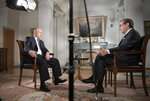 Russian President Vladimir Putin, left, gestures during an interview with