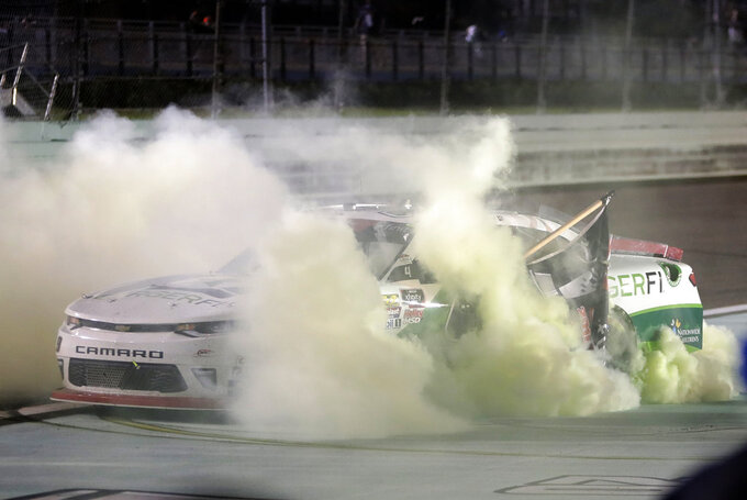 Tyler Reddick does a burnout after winning the NASCAR Xfinity Series championship auto race at the Homestead-Miami Speedway, Saturday, Nov. 17, 2018, in Homestead, Fla. (AP Photo/Lynne Sladky)