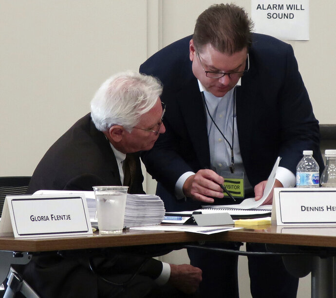 Kansas Supreme Court Nominating Commission members Dennis Hedke, left, and Robert Hayworth, right, confer during a break in its consideration of applicants for a vacant seat on the state's highest court, Friday, Oct. 18, 2019, in Topeka, Kan. The commission's three finalists include a trial-court judge opposed by the state's most influential anti-abortion group. (AP Photo/John Hanna)