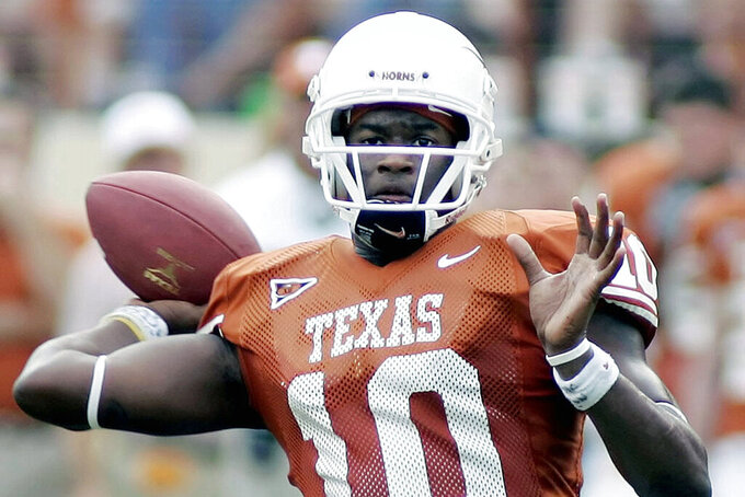 FILE - In this Nov. 12, 2005, file photo, Texas quarterback Vince Young looks to pass against Kansas during the second quarter of an NCAA college football game in Austin, Texas. Newly elected College Football Hall of Famers Darren McFadden, Vince Young and Lorenzo White never won the Heisman Trophy. Each was up for the award at a time when their credentials didn't quite fit the voting trends. (AP Photo/Eric Gay, File)