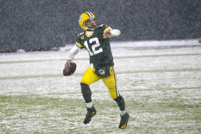 Green Bay Packers' Aaron Rodgers runs for a first down during the second half of an NFL football game against the Tennessee Titans Sunday, Dec. 27, 2020, in Green Bay, Wis. (AP Photo/Mike Roemer)