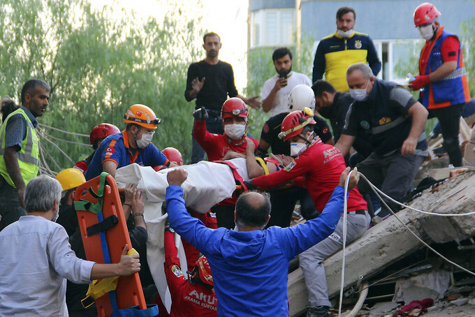 Rescuers carry a man rescued from the debris of his collapsed house, in Izmir, Turkey, Friday Oct. 30, 2020. A strong earthquake struck Friday in the Aegean Sea between the Turkish coast and the Greek island of Samos, killing several people and injuring hundreds amid collapsed buildings and flooding. (Sadik Cangel/IHA via AP)