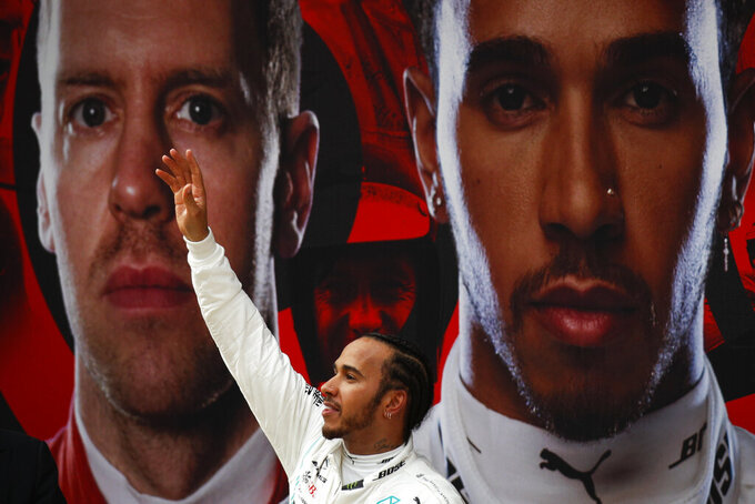 Mercedes driver Lewis Hamilton of Britain waves to his fans after winning the Chinese Formula One Grand Prix at the Shanghai International Circuit in Shanghai on Sunday, April 14, 2019. Vettel finished third. (AP Photo/Andy Wong)