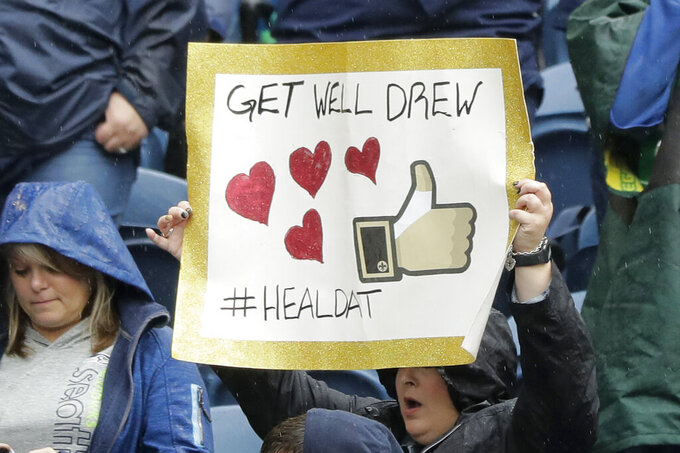 "A fan holds up a sign that reads ""Get Well Drew #HEALDAT"" in support of injured New Orleans Saints quarterback Drew Brees before an NFL football game between the Seattle Seahawks and the Saints, Sunday, Sept. 22, 2019, in Seattle. (AP Photo/Ted S. Warren)"