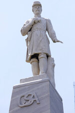 A figure of a Confederate officer, erected in 1913 in Greenwood, Miss., by the Varina Jefferson Davis Chapter of the United Daughters of the Confederacy, in Greenwood, Miss., sits on the lawn of the Leflore County Courthouse, July 14, 2021. For more than a century, one of Mississippi's largest and most elaborate Confederate monuments has looked out over the lawn at the courthouse in the center of Greenwood. It's a Black-majority city with a rich civil rights history. Officials voted last year to remove the statue, but little progress has been made to that end. (AP Photo/Rogelio V. Solis)