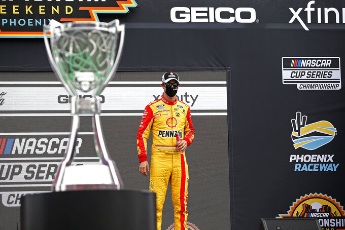 Joey Logano stands on the Championship 4 stage during driver introductions prior to the NASCAR Cup Series auto race at Phoenix Raceway, Sunday, Nov. 8, 2020, in Avondale, Ariz. (AP Photo/Ralph Freso)